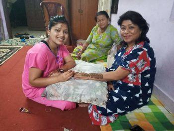 Ayusha bemalt die Hände ihrer neuen Heimmutter Rajya